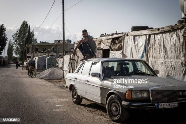 Syrian man is pictured as he sit on a car outside the Al Marj refugee camp