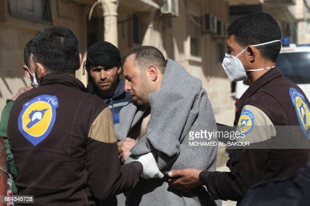 A Syrian man is taken by civil defence workers to a small hospital in the town of Maaret alNoman following a suspected toxic gas attack in Khan...