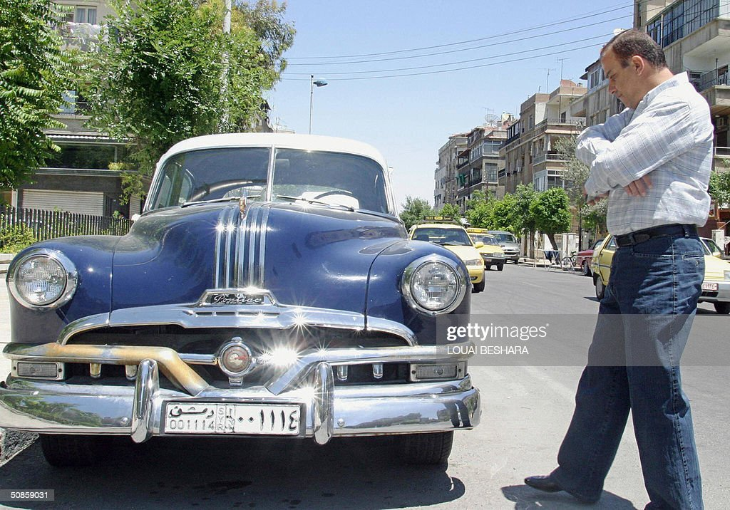 Syrian man looks at a 1953 Pontiac parked in one Damascus' residential neighborhoods 20 May 2004. Old cars from the 1950s and 60s are not a rare sight in the Syrian capital, where taxes on new cars can go as high as 500 percent which makes them out of reach for ordinary Syrians. AFP PHOTO/Louai BESHARA