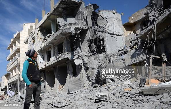 Syrian man looks at a damaged building in the northwestern border town of alBab on February 24 2017 after Turkishbacked rebels announced the...