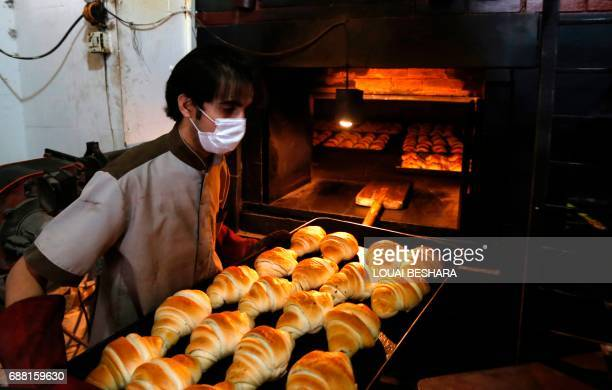 A Syrian man makes croissants in the old city of Damascus on May 25 ahead of the start of the Muslim holy fasting month of Ramadan / AFP PHOTO /...