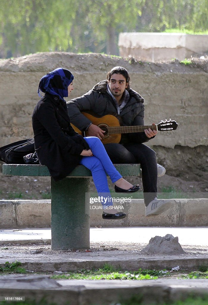 A Syrian man plays his guitar for a woman in Damascus on February 13, 2013. Syria's state news agency SANA cited electricity minister Imad Khamis as saying widespread blackouts have caused economic losses of around $2.2 billion since March 2011. AFP PHOTO/LOUAI BESHARA
