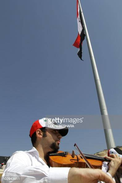 A Syrian man plays the violin during the ceremony of raising a Syrian flag on a 107metre pole over Damascus to celebrate President Bashar alAssad's...