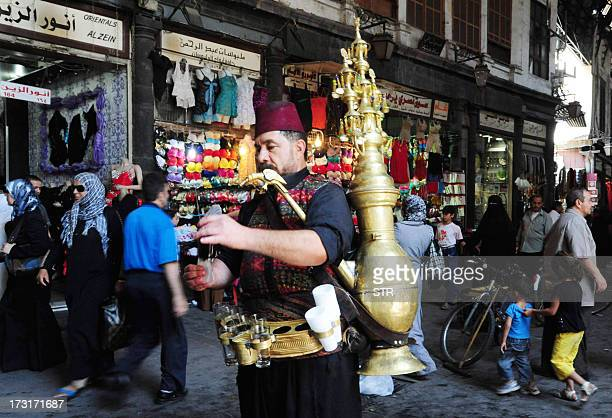 A Syrian man pours a traditional drink in central Damascus on July 9 2013 as Syrians shop in preparation for the Muslim holy fasting month of Ramadan...