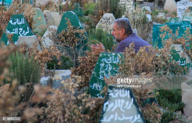 Syrian man prays on July 12 2017 at a cemetary in Khan Sheikhun a rebelheld town in the northwestern Syrian Idlib province 100 days following a...