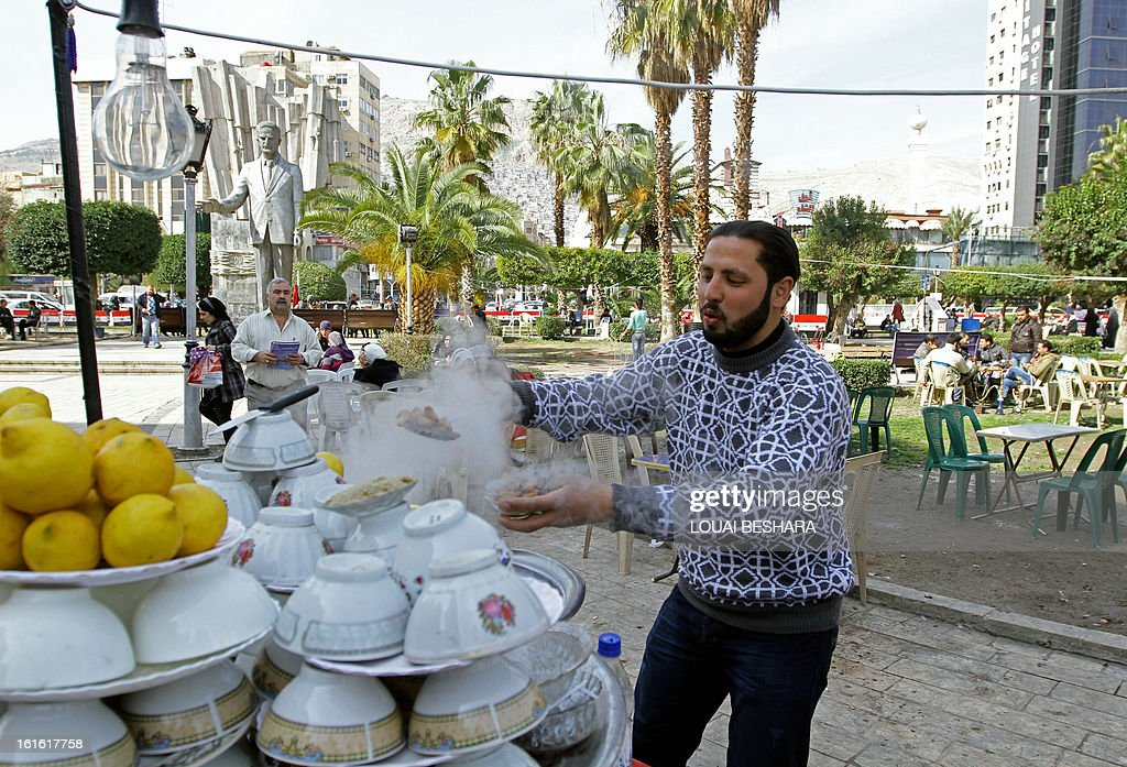 A Syrian man prepares street food at his stall in Damascus on February 13, 2013. Syria's state news agency SANA cited electricity minister Imad Khamis as saying widespread blackouts have caused economic losses of around $2.2 billion since March 2011.