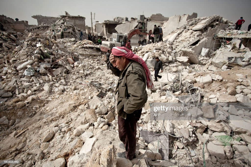 A Syrian man reacts while standing on the rubble of his house while others look for survivors and bodies in the Tariq alBab district of the northern...