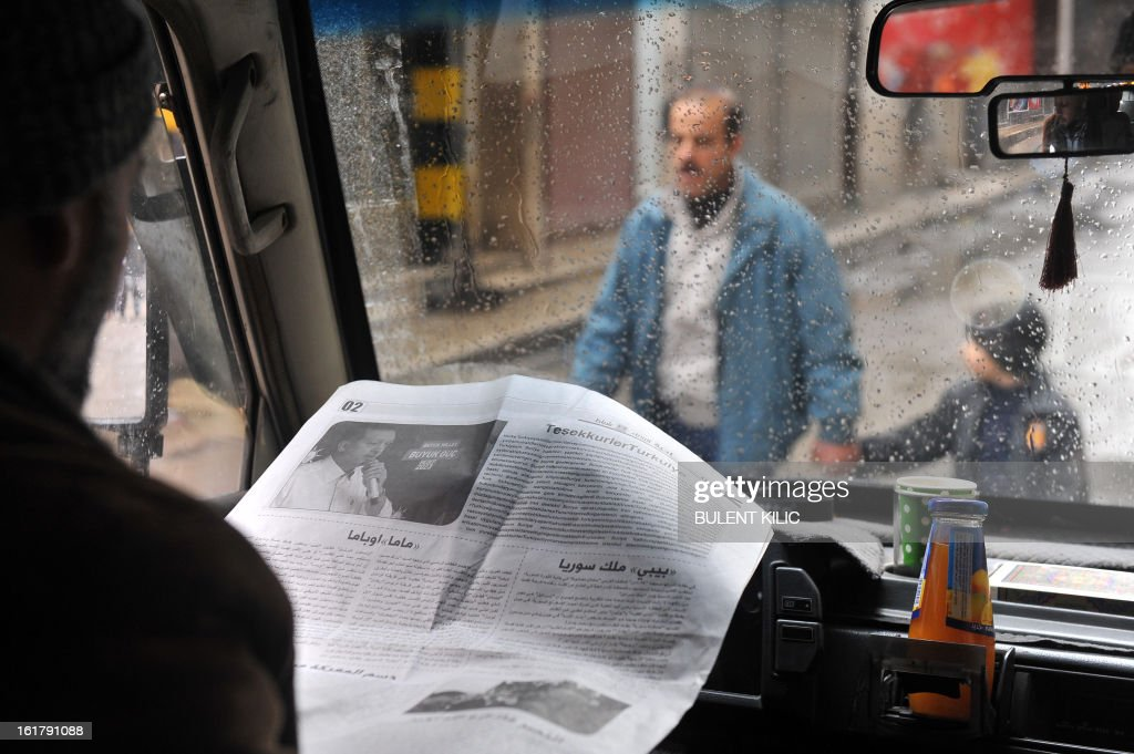 A Syrian man reads in his truck an opposition newspaper featuring Turkish Prime Minister in the northern city of Aleppo on February 16, 2013. More than 300 people were abducted by armed groups in northwestern Syria over two days in an unprecedented string of sectarian kidnappings, a watchdog and residents said.