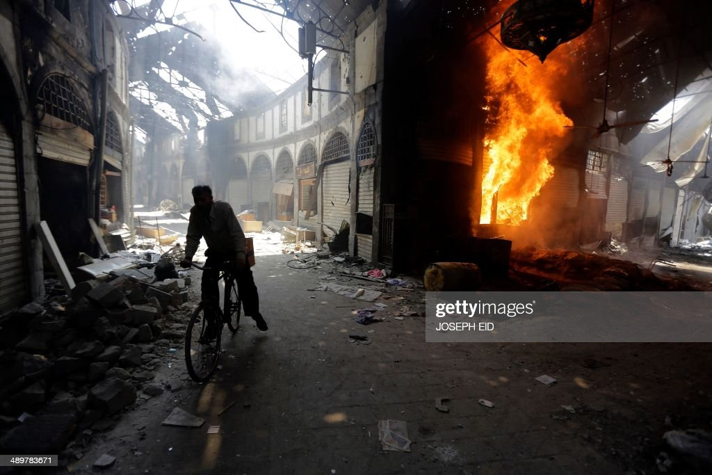 A Syrian man rides his bicycle past a burning shop at the Maskuf market in the old city of Homs on May 12 2014 Syrians streamed back into the ruins...