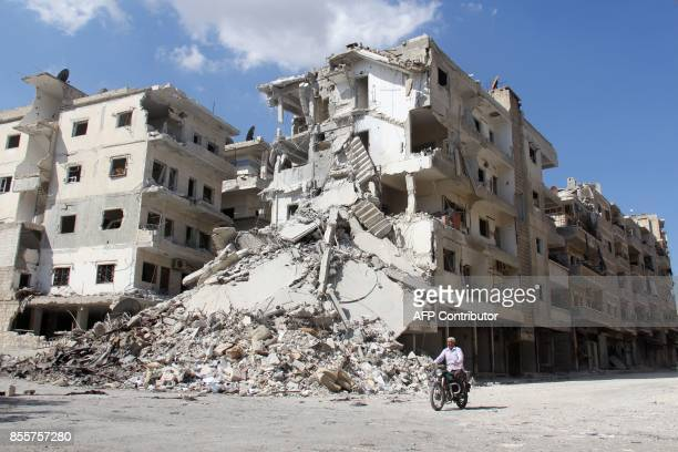 Syrian man rides his bicycle past a destroyed building in the district of Jisr alShughur in the northwestern Idlib province on September 29 2017 /...