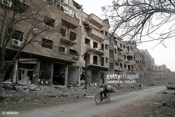 Syrian man rides his bicycle past damaged buildings in rebelheld part of Jubar neighbourhood in the Syrian capital Damascus on March 9 2016 / AFP /...