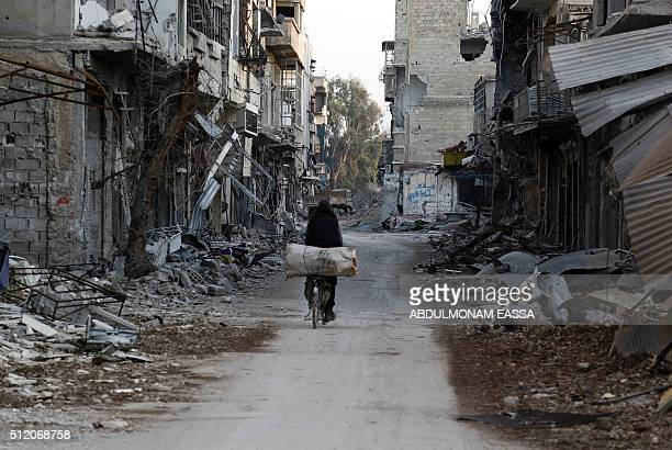 Syrian man rides his bike along a street damaged by shelling in the rebelheld part of Jubar neighbourhood in the Syrian capital Damascus on February...