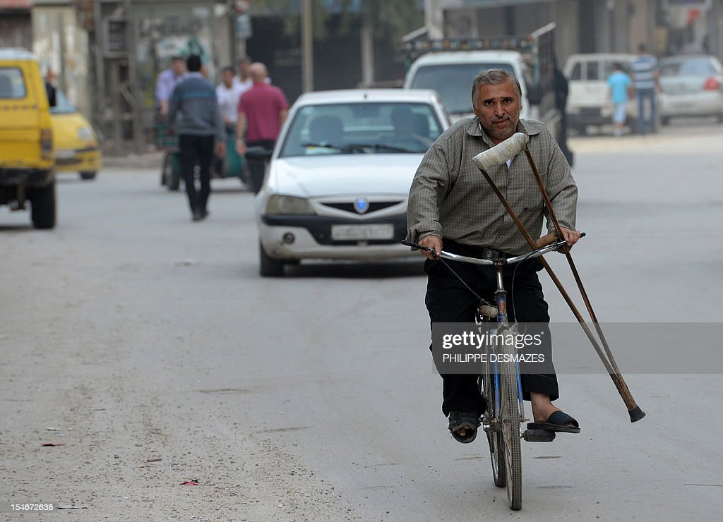 A Syrian man rides his bike, holding a crutch, along a street in Syria's northern city of Aleppo, on October 24, 2012. The UN Security Council called on the Syrian government and opposition to heed peace envoy Lakhdar Brahimi's appeal for a ceasefire in their 19-month-old war. AFP PHOTO/PHILIPPE DESMAZES