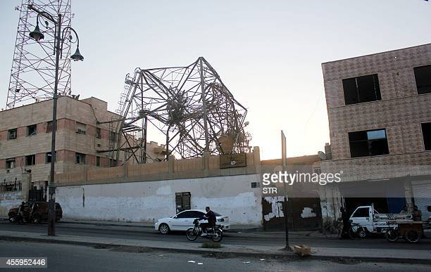 A Syrian man rides his bike past a communications tower that was destroyed after a US drone crashed into it according to fighters with the Islamic...