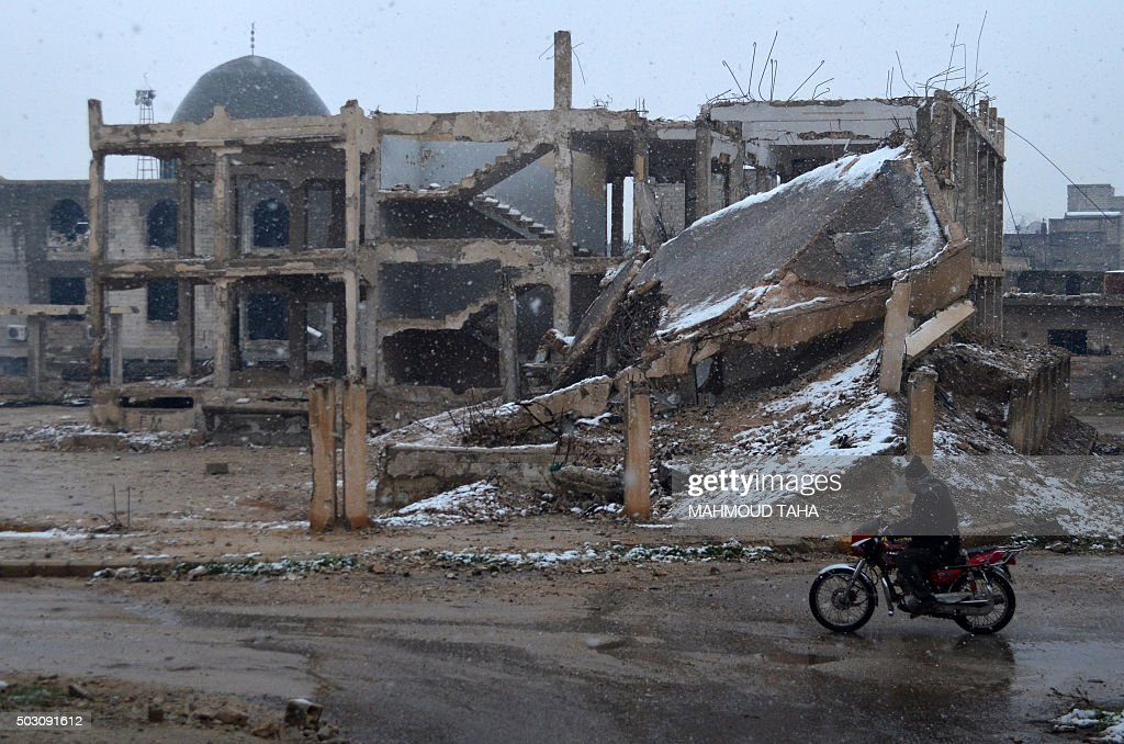 A Syrian man rides his motorbike past a damaged building covered with snow on January 1 2016 in the central Syrian town of Talbisseh in the Homs...