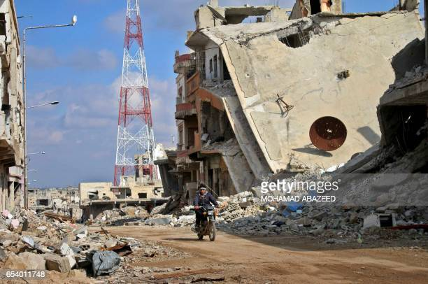 Syrian man rides his motorcycle past damaged buildings in the southern city of Daraa on March 16 2017 Daraa province the cradle of the 2011 uprising...