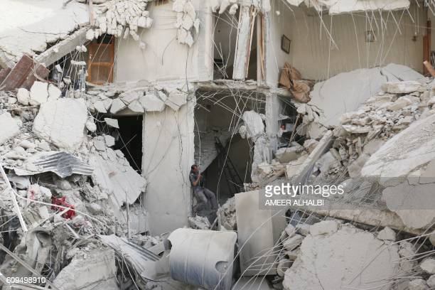 A Syrian man searches for victims through the rubble of a destroyed building following a reported air strike in the Qatarji neighbourhood of the...
