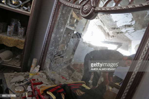 Syrian man seen reflected in a mirror gathers his belongings from his damaged home following a reported airstrike on March 29 in the eastern Ghouta...
