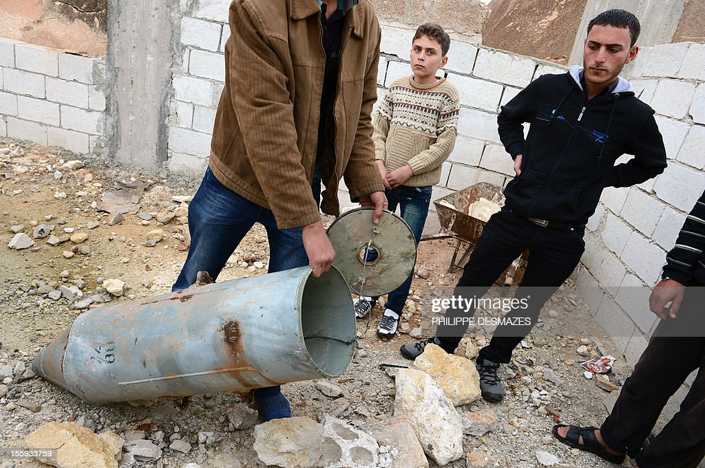 A Syrian man shows a cluster bomb, that releases or ejects smaller sub-munitions, in the northern Syrian town of Taftanaz, in the Idlib province, on November 9, 2012. Syrian President Bashar al-Assad said his future could only be decided at the ballot box and denied Syria was in a state of civil war, despite fresh attacks and heavy fighting near the Turkish border.