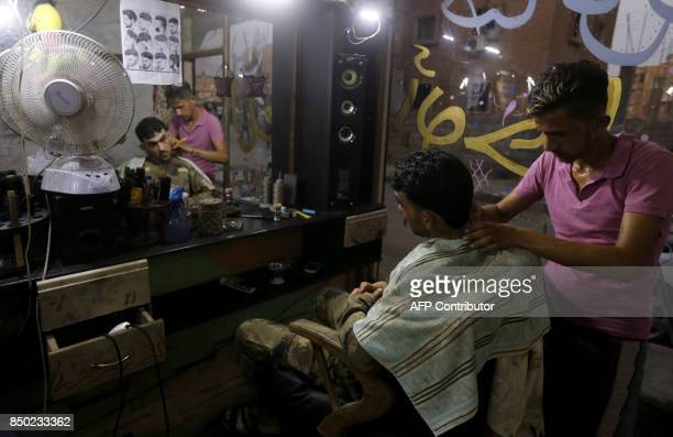 A Syrian man sits at a barbershop in the eastern city of Deir Ezzor on September 20 2017 as Syrian government forces continue to press forward with...