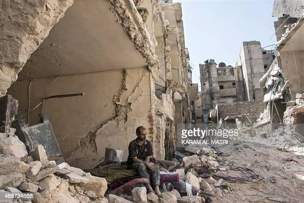 Syrian man sits in the rubble following a barrel bomb attack the previous day on the rebelheld neighbourhood of alMashad in the northern Syrian city...