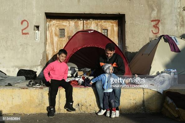 A Syrian man sits with two young boys outside a tent with other migrants and refugees gathered at the pier of the port of Piraeus port southwest of...