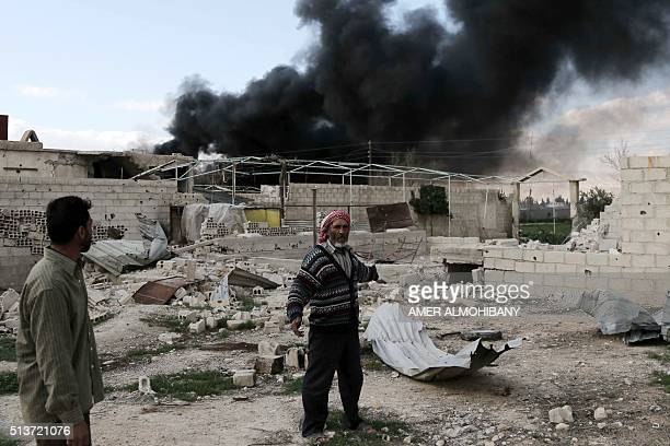 A Syrian man stands in the courtyard of his farm as smoke billows in the background following reported air strikes near the rebelheld village of...