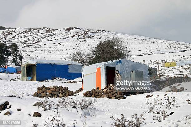 A Syrian man stands in the snow outside his tent after a storm at a makeshift refugee camp near the village of Burayqah on the outskirts of...
