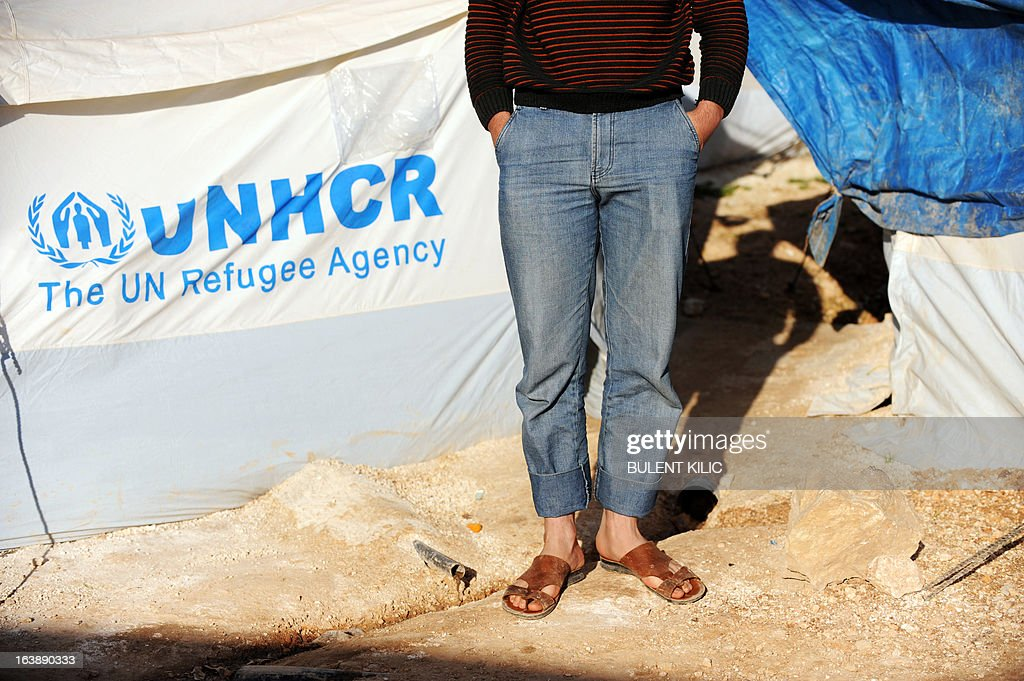 A Syrian man stands next to a sewage pipe outside his makeshift house at the refugee camp of Qah along the Turkish border in the village of Atme in the northwestern province of Idlib, on March 17, 2013. The conflict has killed at least 70,000 people, and forced more than one million Syrians to seek refuge abroad. Millions more have been internally displaced. AFP PHOTO/BULENT KILIC