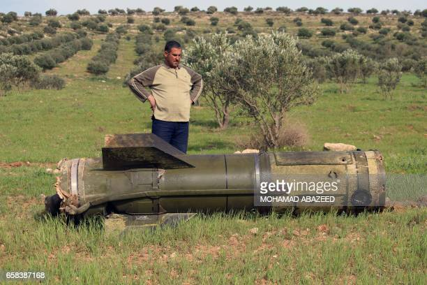 A Syrian man stands next to an unexploded groundtoground missile fired by government forces on the southern Syrian city of Daraa on March 27 2017 /...