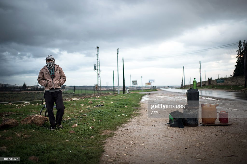 A Syrian man stands next to gas cans at a make-shift gas station on the road to Aleppo, in February 16, 2013. Rebels pressed an offensive in northern Syria on Saturday, attacking Aleppo airport and two airbases, as the Syrian Observatory for Human Rights and residents reported hundreds of people held in a string of sectarian kidnappings. AFPP