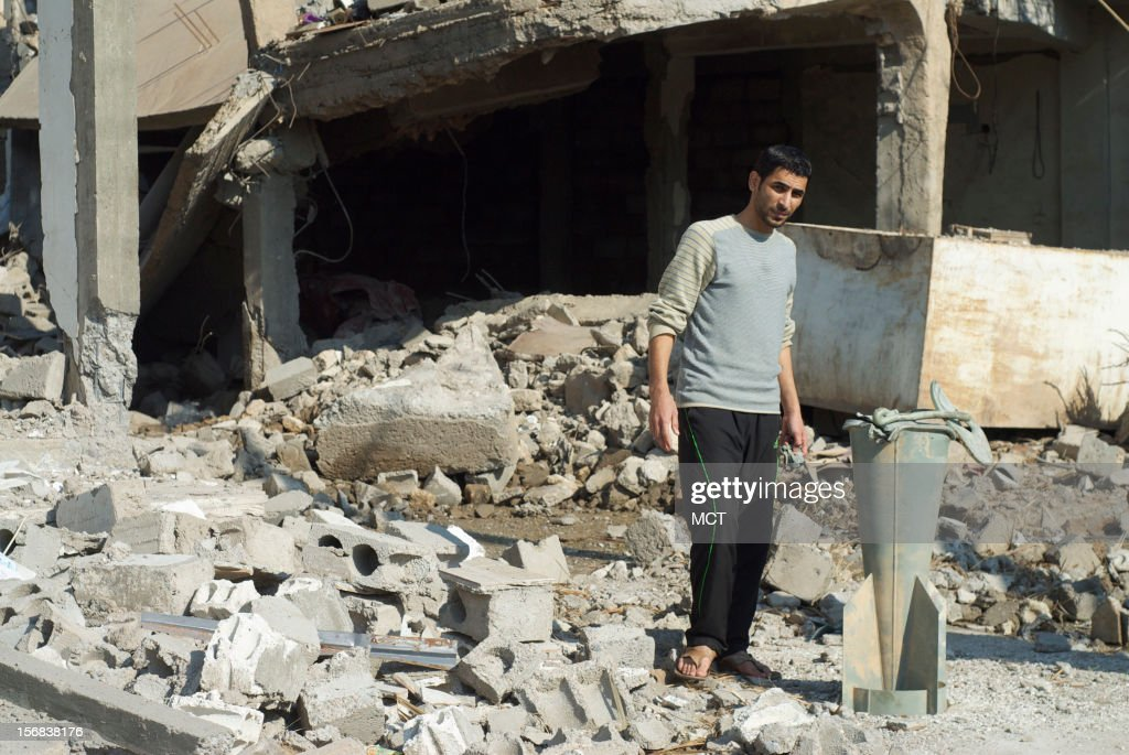 A Syrian man stands next to the remains of a Syrian government cluster bomb, on November 21, 2012, outside of houses it destroyed in Mayadin, in southeastern Syria, on November 10. Both sides of Syria's civil war have escalated the size of the weapons they are using in recent months.