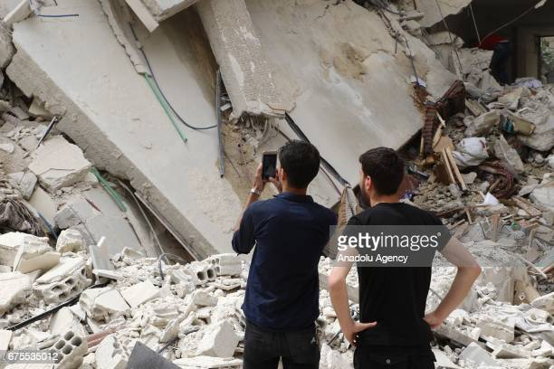 Syrian man takes a photo of collapsed Arbin hospital after Assad Regime's airstrike hit residential areas at the Arbin district of Eastern Goutha in...
