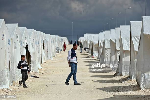 Syrian man walks between tents in Suruc refugee camp on March 25 2015 in Suruc Turkey The camp is the largest of its kind in Turkey with a population...