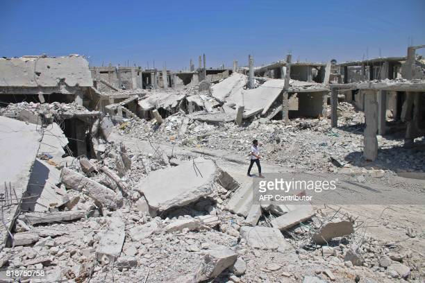 A Syrian man walks down a destroyed street in a rebelheld area in Daraa on July 19 as civilians started to return to the area following the July 9...