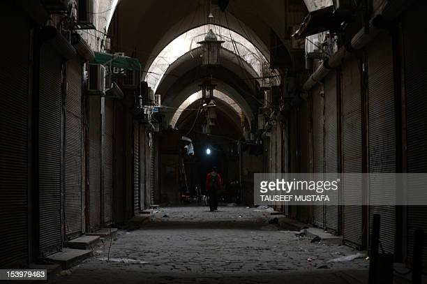 A Syrian man walks in a deserted alley in Aleppo's Old city on October 11 2012 Rebels cut off the highway linking Damascus with Syria's second city...