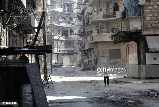 A Syrian man walks in Aleppo's Kallase industrial neighbourhood on July 5 2017 Six months after Syria's army captured the country's onetime economic...