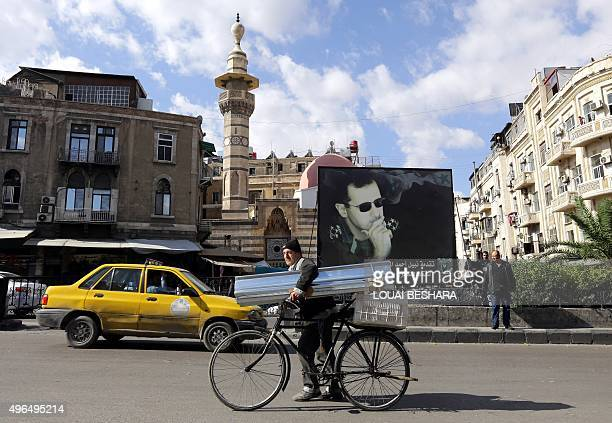 A Syrian man walks past a banner bearing a portrait of Syrian President Bashar alAssad in the Syrian capital Damascus on November 10 2015 AFP PHOTO /...