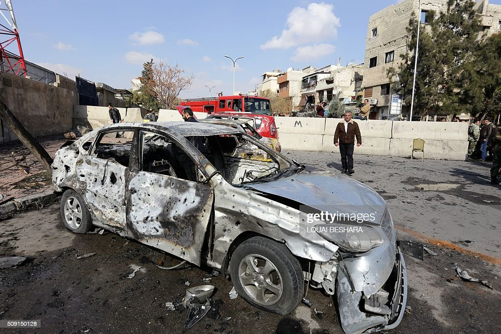 A Syrian man walks past a damaged car at the site of a suicide attack at a police officer's club in the Masaken Barzeh district of the capital Damascus on February 9, 2016. The Syrian Observatory for Human Rights said about 20 people had also been wounded, adding that policemen were among the dead and injured. BESHARA