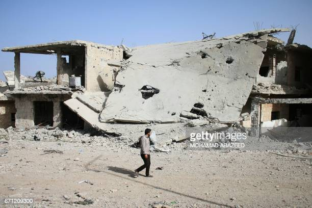 A Syrian man walks past a destroyed building in a rebelheld area in the southern city of Daraa on April 21 2017 / AFP PHOTO / Mohamad ABAZEED