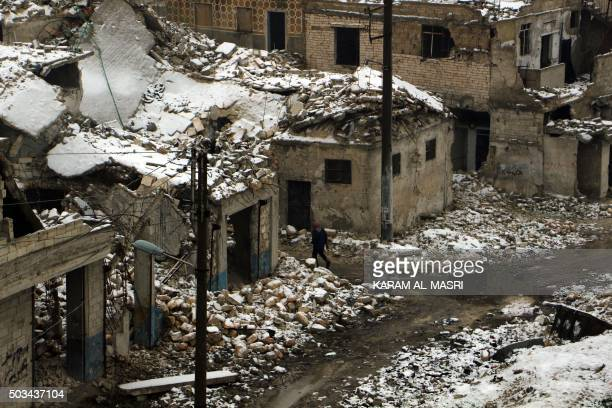 A Syrian man walks past damaged houses following a snow storm in the northern Syrian city of Aleppo on January 5 2016 The conflict in Syria has...