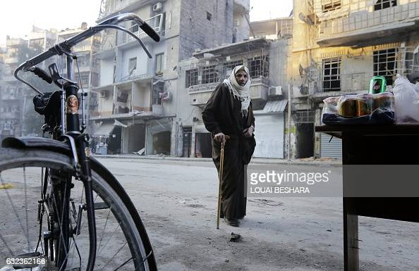 Syrian man walks past destroyed buildings in Aleppo's formerly rebelheld alShaar neighbourhood on January 21 a month after government forces retook...