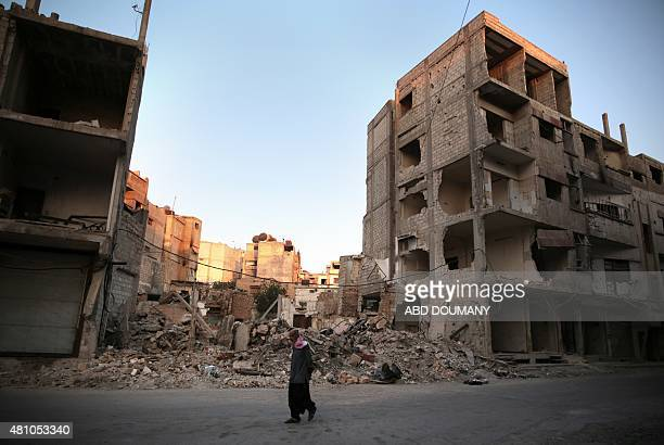 A Syrian man walks past destroyed buildings in the rebelheld area of Douma east of the capital Damascus on July 17 on the first day of Eid AlFitr...