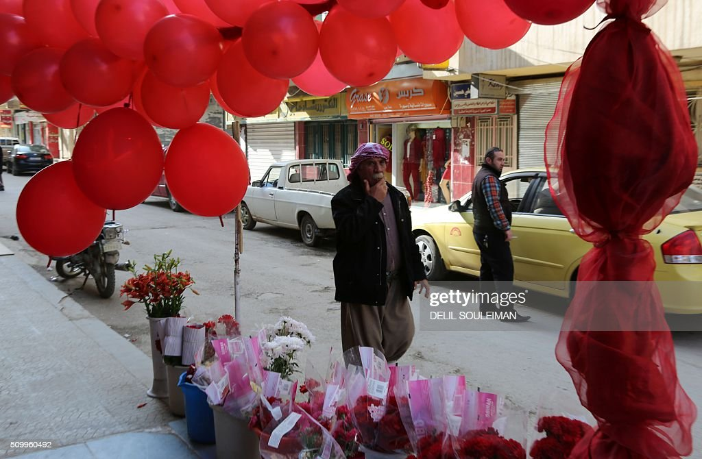 A Syrian man walks past red flowers and balloons as shops display Valentine's day gifts in the northeastern city of Qamishli on February 13, 2016. / AFP / DELIL SOULEIMAN