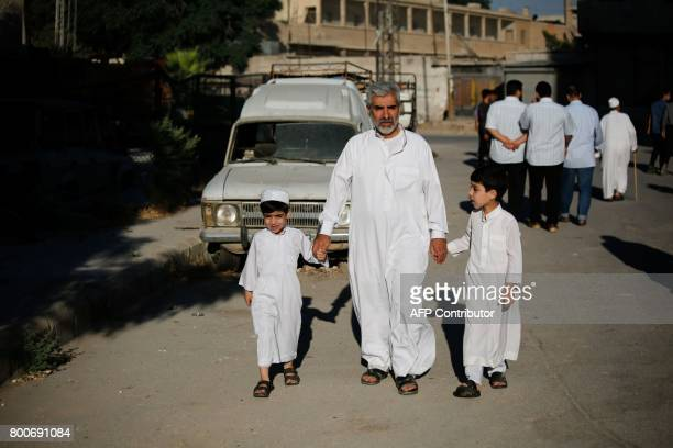 A Syrian man walks with his sons after visiting a cemetary in the rebelcontrolled town of Hamouria in the eastern Ghouta region on the outskirts of...
