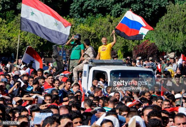 A Syrian man waves a Syrian and Russian flag in Umayyad Square in Damascus as fans gathered to watch a live broadcast of the World Cup qualifying...