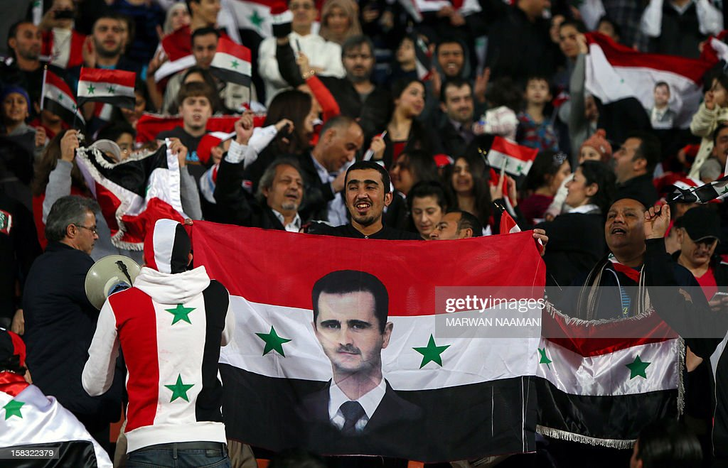 A Syrian man waves his national flag bearing the image of embattled President Bashar al-Assad during his country's team match against Iraq in the 7th West Asia Football Federation (WAFF) championship in Kuwait City on December 13, 2012.