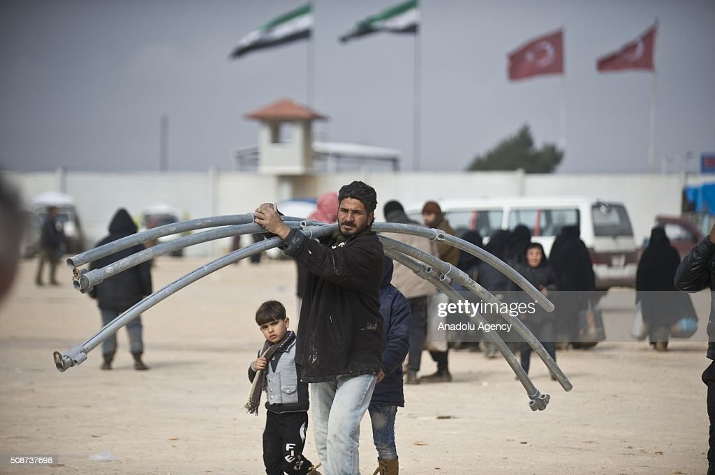 A Syrian man who fled bombing in Aleppo, carries equipment to set up a tent, which was distributed by the IHH Humanitarian Relief Foundation, a Turkish NGO, at the Oncupinar crossing, opposite the Turkish province of Kilis, near Azaz town of Aleppo, Syria on February 6, 2016. Thousands of Syrians have massed on the Syrian side of the border seeking refuge in Turkey.