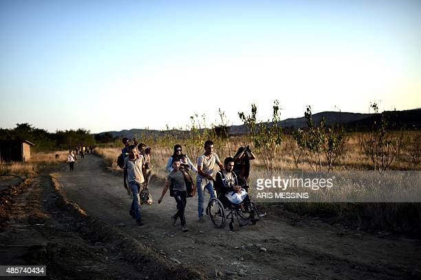 A Syrian man who lost his legs after shelling near Damascus is helped by other migrants as they walk at a field after crossing the border from Greece...