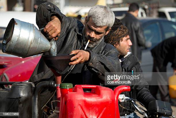 A Syrian man who set up up a business outside a destroyed petrol station pours petrol for sale into a plastic bottle in the alFardos neighbourhood of...